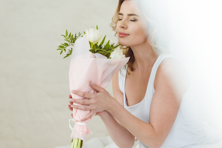 beautiful woman sniffing bouquet of flowers for international womens day Imagens