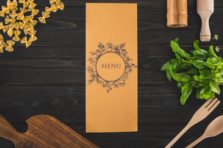 top view of restaurant menu, ingredients and utensils on wooden table Stock Photo