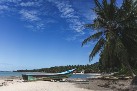 tranquil tropical beach with old boat on sunny day