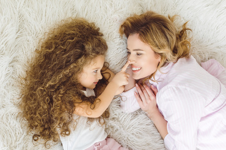 top view of adorable curly daughter touching nose of her mom 写真素材