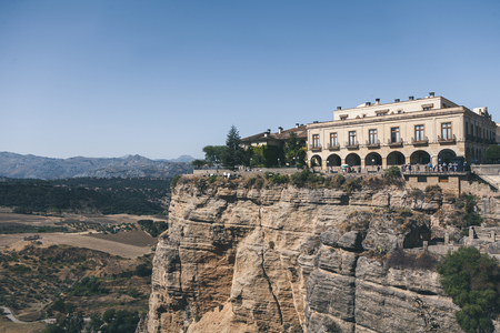 scenic view of building on rock against mountains landscape, Ronda, spain Stock Photo