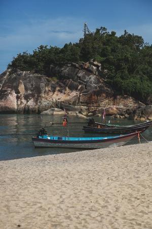 rocky coast near sandy beach with old boat on sunny day