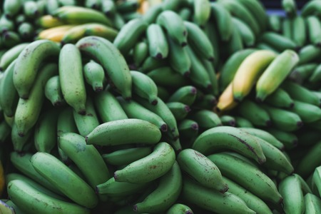 close-up shot of pile of green bananas branches selling on market Stock Photo