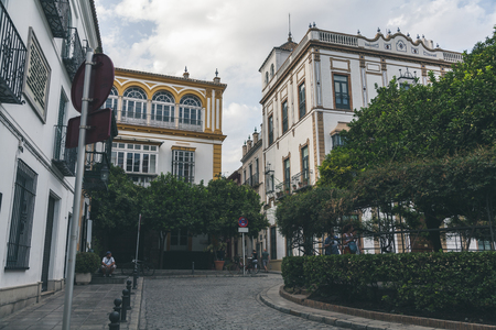 view of city street with trees and buildings under cloudy sky, spain Editorial