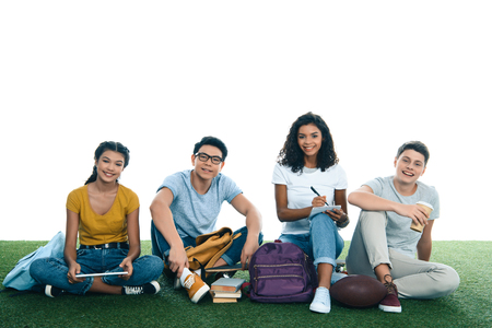 group of teen students studying while sitting on grass isolated on white 스톡 콘텐츠