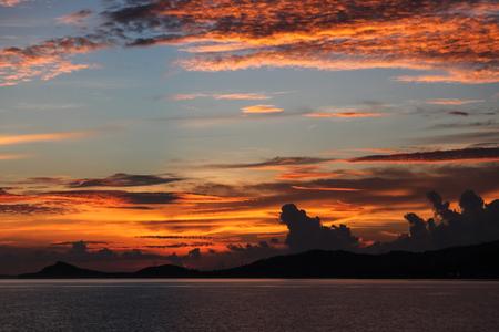 beautiful orange clouds on blue sky over evening seascape Фото со стока