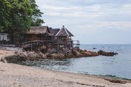 cozy wooden shacks at sea coast on cloudy day Фото со стока