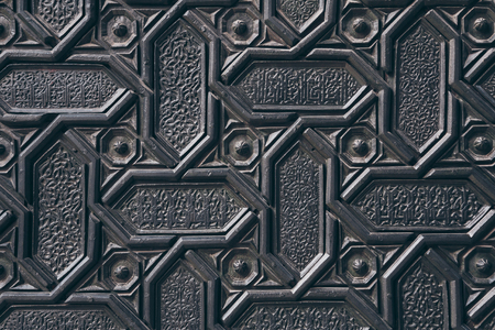 close-up shot of black wall with carved arabesque pattern