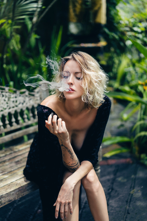blond woman in black clothing smoking cigarette while resting on bench on terrace, ubud, bali, indonesia
