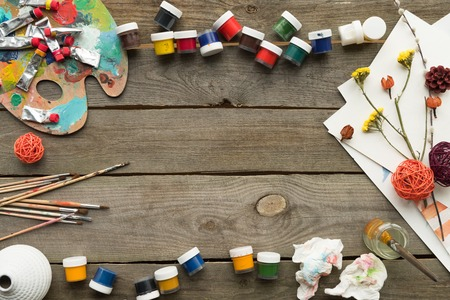 Top view of containers with poster paints on a wooden surface
