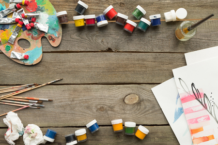 Top view of containers with poster paints on a wooden table