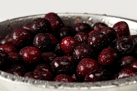 close-up shot of fresh ripe sweet cherries in metal colander on white surface