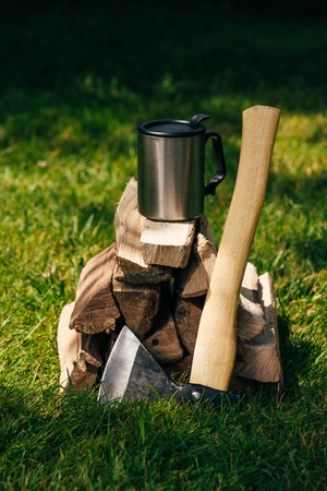 thermos bottle on pile of firewood on green grass in park 写真素材