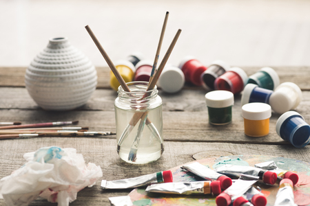 Paint brushes in a solvent and scattered containers with poster paints and acrylic paints tubes Foto de archivo