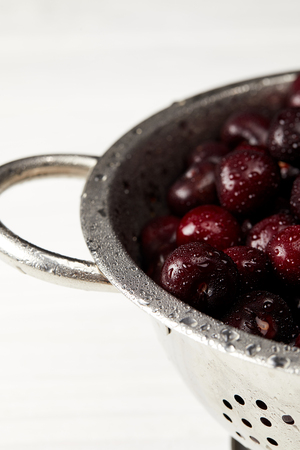 close-up shot of fresh ripe cherries in metal colander on white tabletop Stock Photo