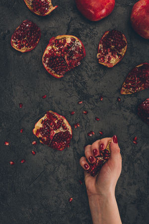 Cropped image of woman holding pomegranate piece in hand