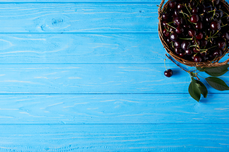 top view of red cherries in basket on blue wooden surface