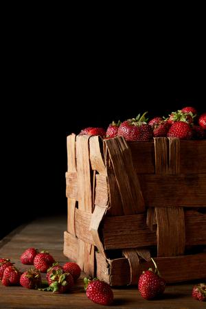 freshly harvested strawberries in rustic box on black
