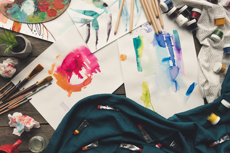 Top view of scattered painter sketches on a wooden table