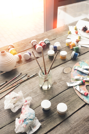 Paint brushes in a water and scattered containers with poster paints Stock Photo