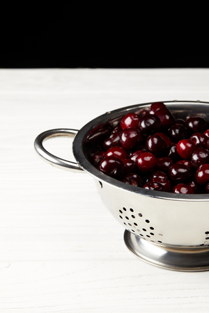 red ripe sweet cherries in metal colander on white wooden surface and on black