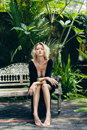 blond woman in black clothing with cigarette in hand resting on bench on terrace, ubud, bali, indonesia Stock Photo