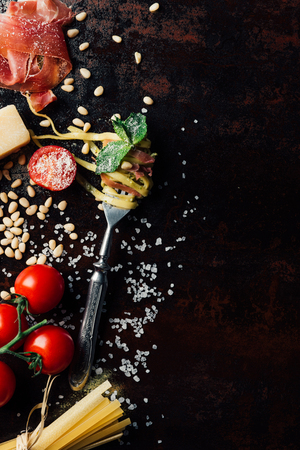 top view of fork wrapped by pasta with mint leaves, jamon, pine nuts,  and cherry tomatoes covered by grated parmesan on table surrounded by ingredients Reklamní fotografie