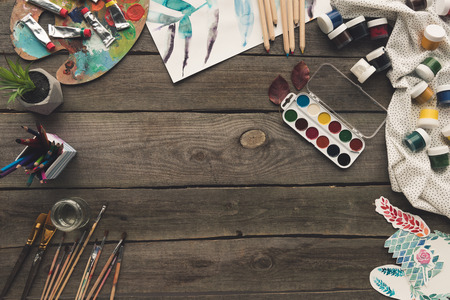 Top view of wooden table with paints and sketches
