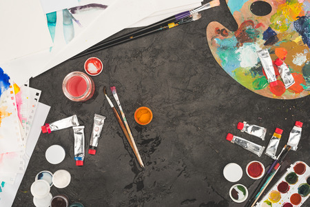 Top view of brushes and paints on a concrete table