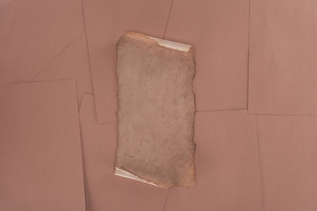 top view of old damaged paper over brown paper background