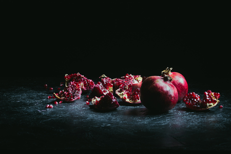 pomegranate pieces and seeds on a dark surface