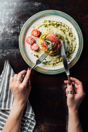 partial view of woman eating pasta with mint leaves, jamon, pine nuts, pesto and cherry tomatoes covered by grated parmesan at table