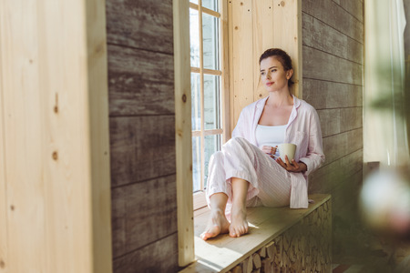thoughtful woman in pajamas holding cup of coffee and sitting on windowsill