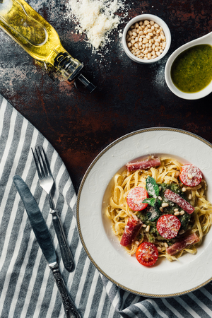 elevated view of pasta with mint leaves, jamon and cherry tomatoes covered by grated parmesan on plate at table with kitchen towel, knife, fork, olive oil, pine nuts and pesto in bowl Reklamní fotografie
