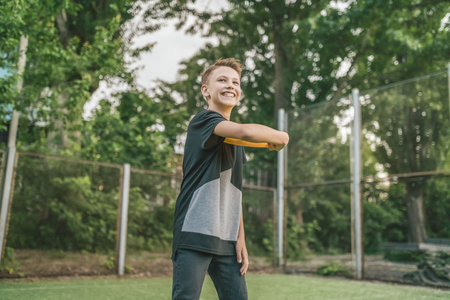 beautiful smiling boy playing with flying disc and looking away outdoors Stok Fotoğraf