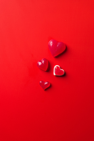 top view of heart shaped candies on red surface