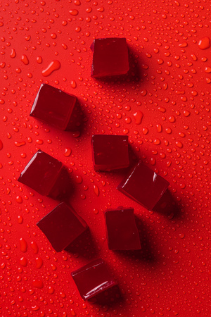 top view of candies on red surface with water drops