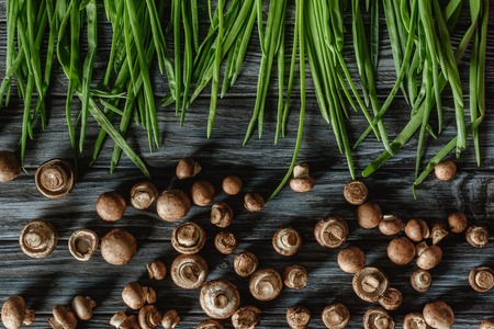 top view of champignon mushrooms with leeks on wooden tabletop Banco de Imagens