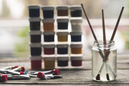 Paint brushes in a liquid and containers with poster paints