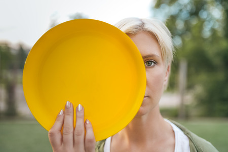 beautiful blonde woman holding yellow flying disk and looking at camera