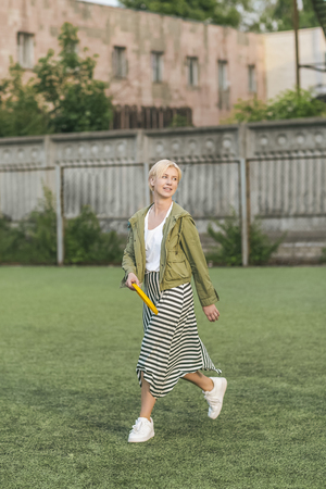 beautiful blonde woman holding flying disc and looking away Stok Fotoğraf - 104791078