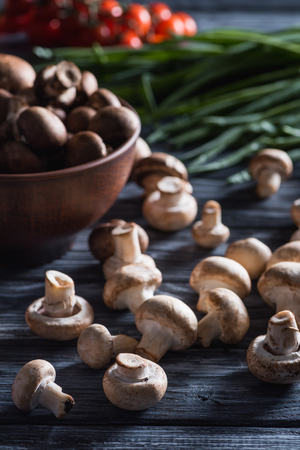 close-up shot of delicious raw champignon mushrooms with leek on dark wooden table Foto de archivo - 104786979