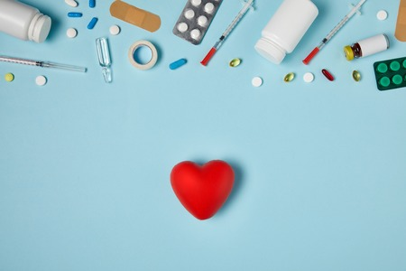 top view of heart and various medicines on blue surface