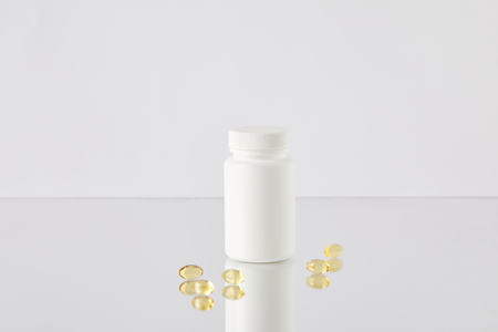omega fish hat supplement capsules with blank jar on reflective surface and on white