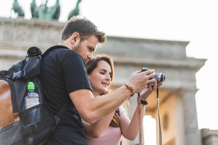 low angle view of tourists looking at photo camera in front of Brandenburg Gate, Berlin, Germany