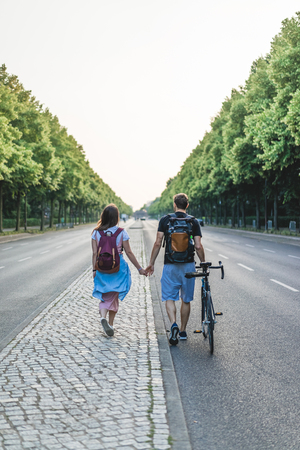 rear view of couple with backpacks and bicycle walking at street