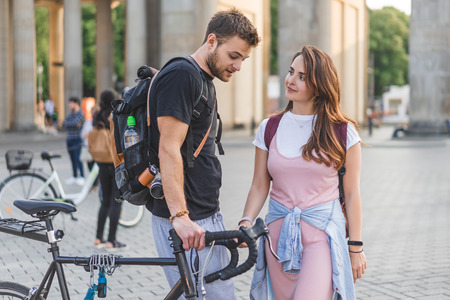 couple of tourists with backpacks and bicycle at Pariser Platz in Berlin, Germany Stock Photo