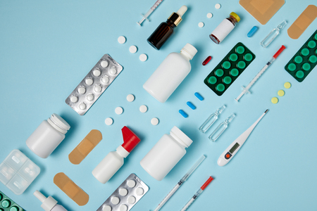 top view of various medical supplies composed in row on blue surface