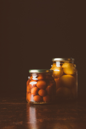 glass jars with preserved red and yellow tomatoes on wooden table in dark kitchen Zdjęcie Seryjne