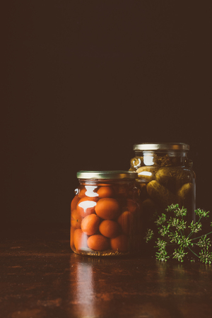 glass jars with preserved tomatoes and cucumbers on wooden table in dark kitchen
